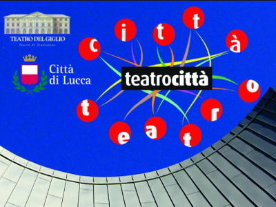 TeatroCittà review logo blue sky above part of concrete building below. On the part of the sky, logo of the teatro del giglio, logo of the municipality of Lucca, blue sky with logo written teatrocittà white on a black strip with colored stripes that end in the shape of a red circle inside which there is a white letter that makes up the word teatrocittà